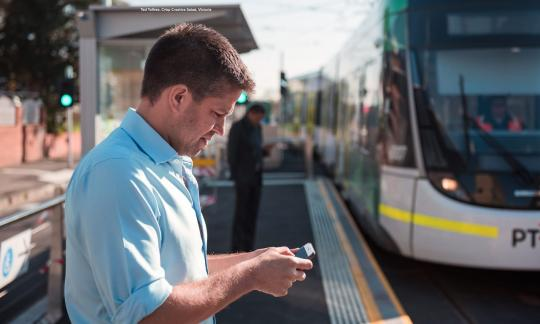 man standing at a train platform whilst using his mobile