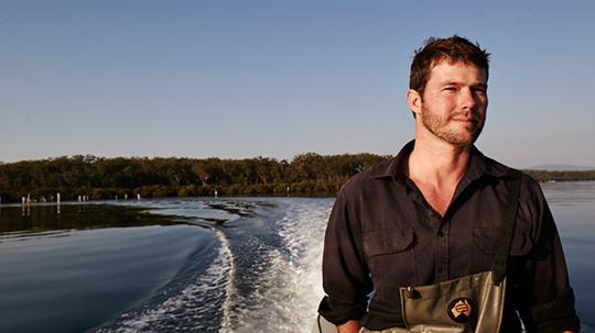 Ewan of McAsh Oysters and Ulladulla Oyster Bar in a black shirt on the water