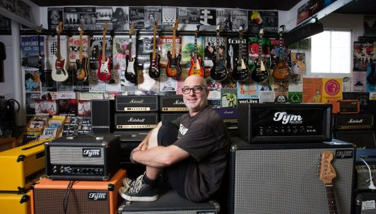 man sat in music store with records and speakers around him