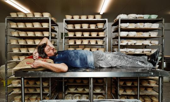man lying down on meet table in bakery