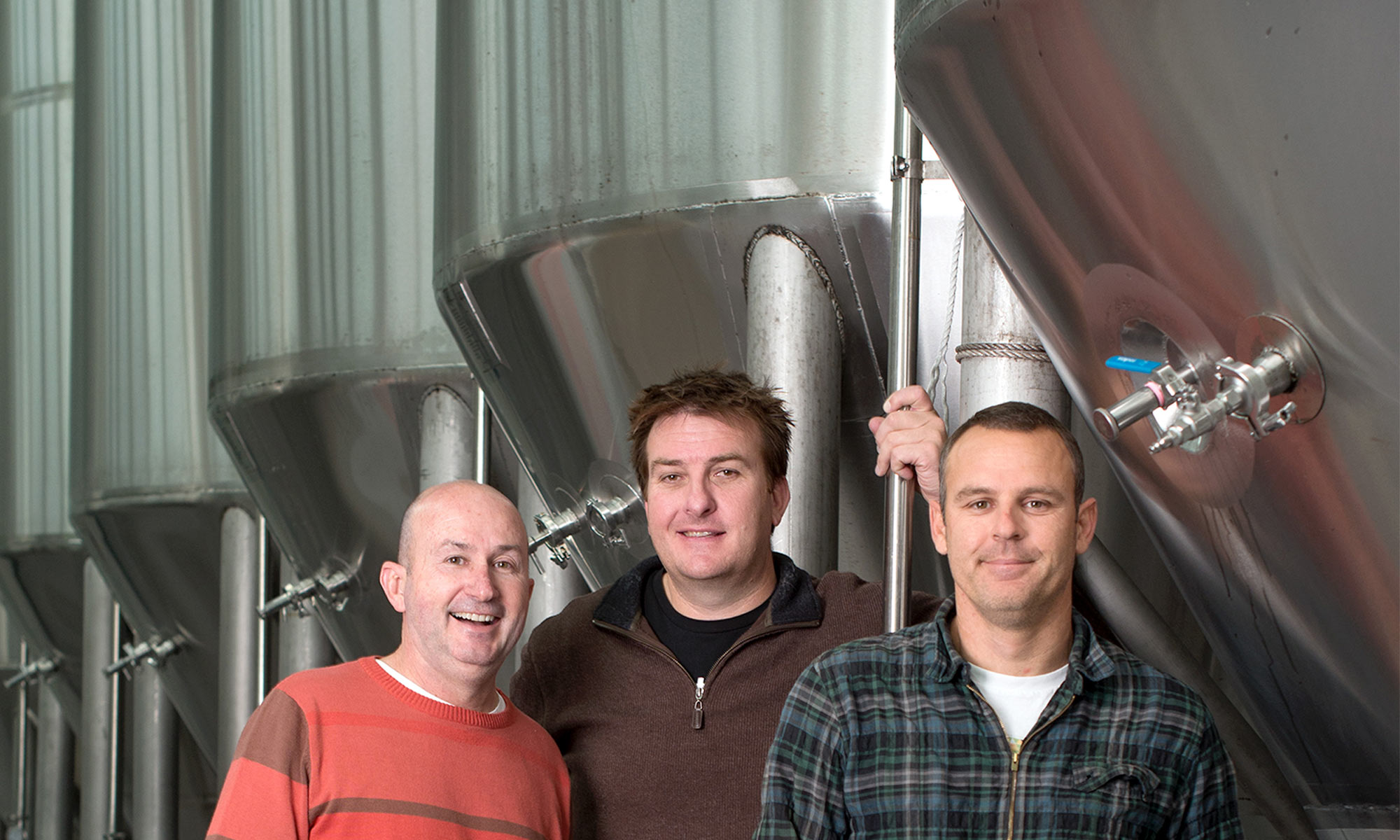 three men stood in front of brewing distillers