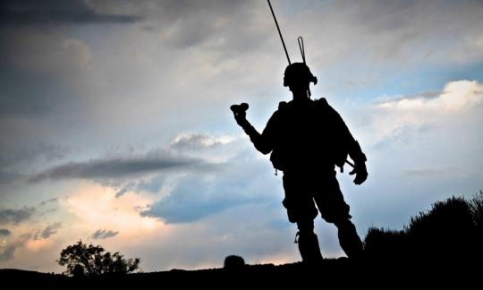 silhouette of man kitted out in army attire against sky backdrop