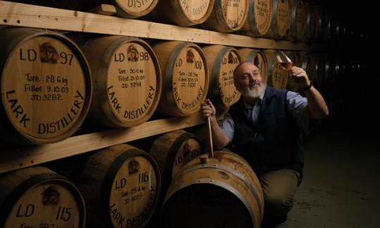 Bill Lark with a glass of whisky in cellar full of barrels