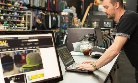 man operating laptop at till of his clothes store