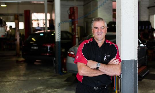 man leaning against pillar in car mechanical garage