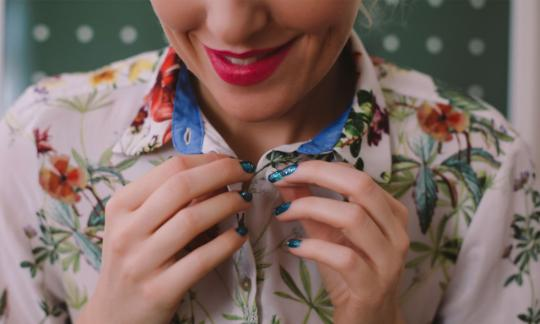 Woman buttoning up the collar of a floral shirt
