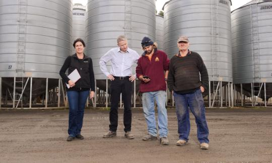 four workers stood in front of grain silos