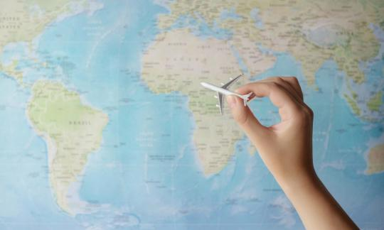 map of the world with miniature plane being pushed across