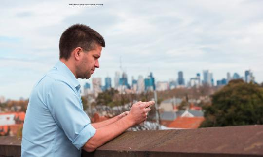 Man looking at mobile phone with city scape in the backdrop