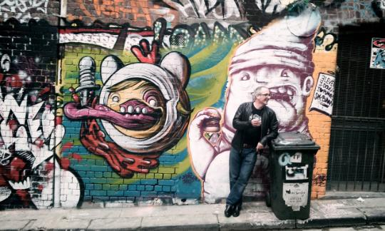 man leaning against bin with graffiti wall behind him