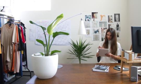 women sat at desk with plants and clothes sketches around her