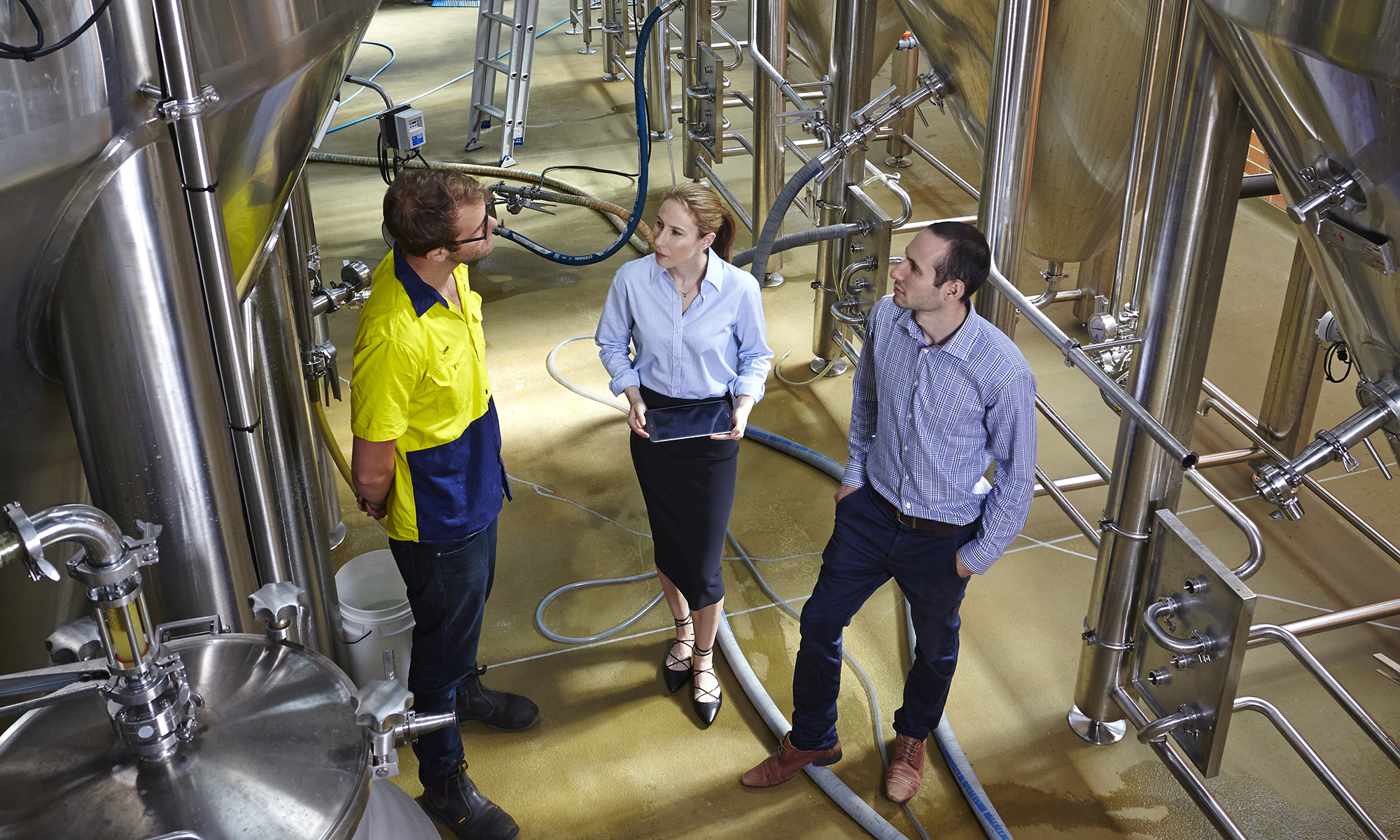three workers having a discussion in distillery plant