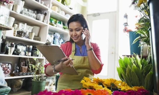 woman on phone with clipboard in flower shop
