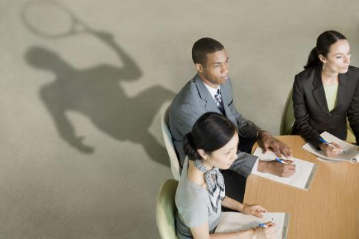 Image shows three business people sitting around a table at a meeting with the man's shadow swinging a tennis racket.