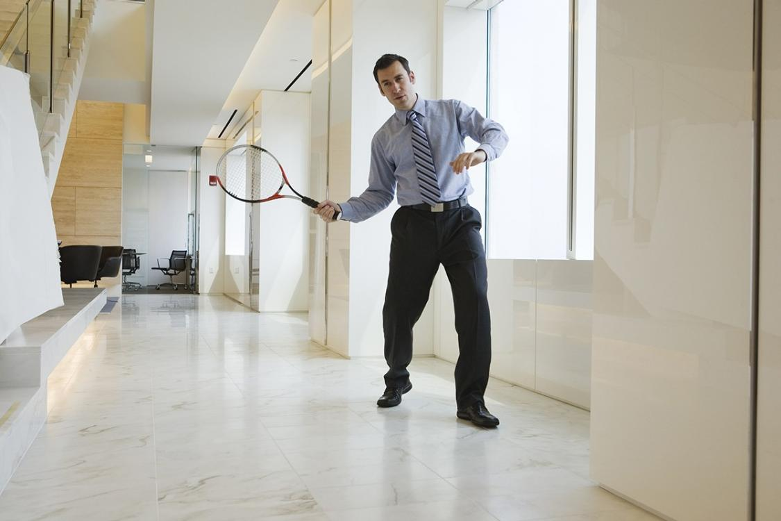 man playing tennis in corridor