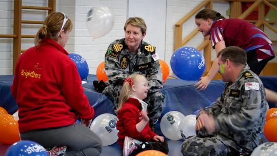 military playing with disabled child amongst balloons