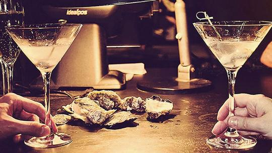 Cocktails and Oysters with hands holding them