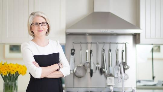 Georgia Cleary in the kitchen of a house with flowers and utensils