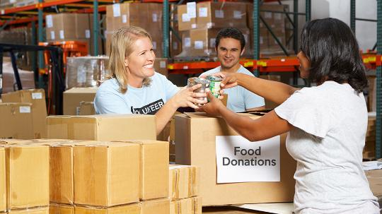 "3 people exchanging food donations over a box labelled ""food donations"""