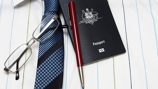 Business shirt with tie, glasses, pen and passport