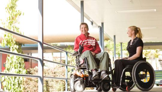 two people in wheelchairs smiling