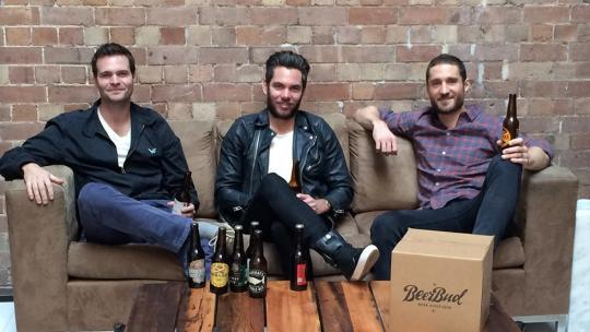 three men sitting on a couch drinking beer