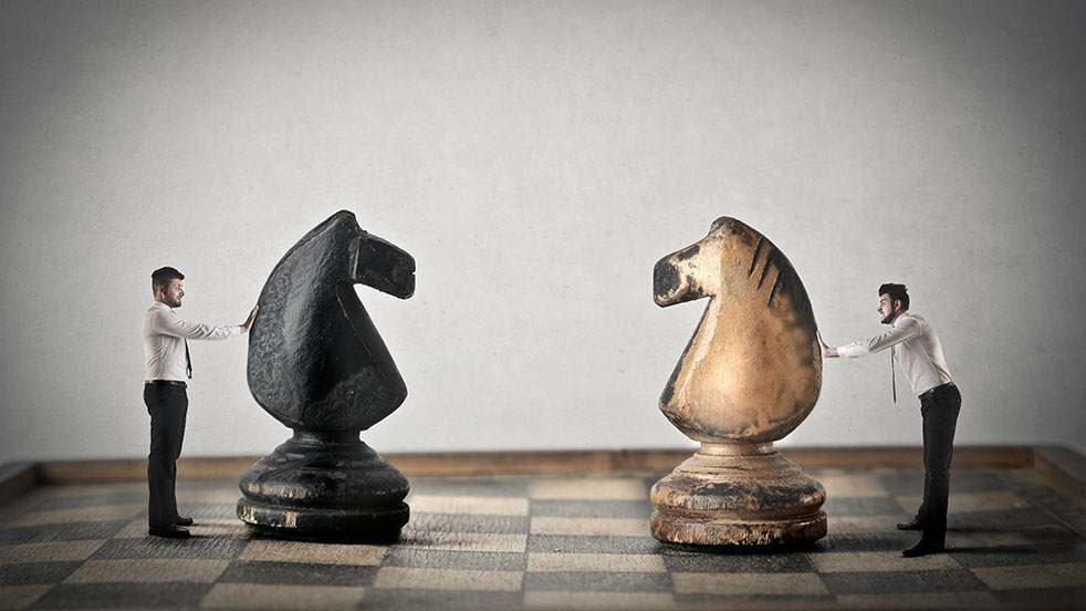 men pushing chess pieces