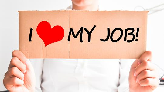 woman holding cardboard saying i love my job