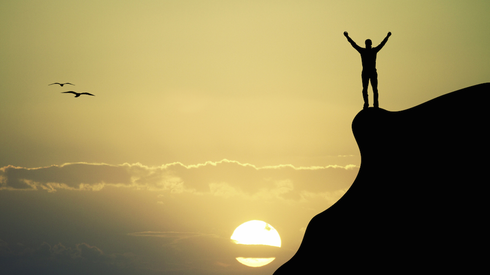 Man standing on cliff with arms upraised