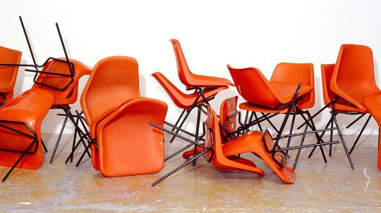 Orange chairs in a pile