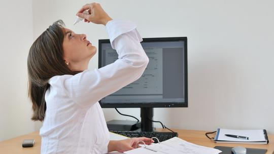 woman putting in eyedrops at her desk with computer