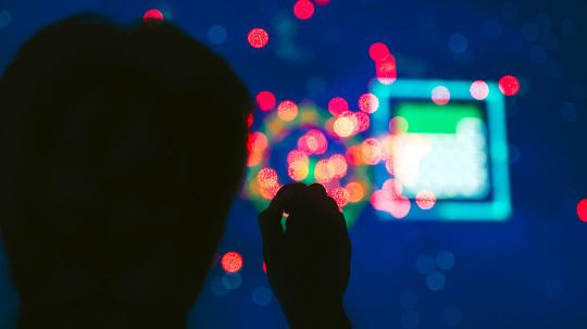 A shot from behind of a person in front of a mass of coloured lights and shapes