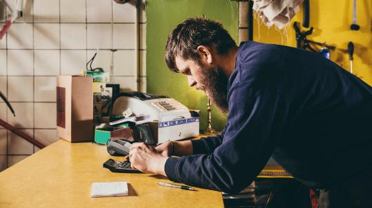 Man using calculator on workshop counter