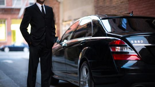 man wearing suit next to black car
