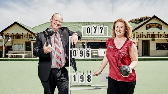 Keith Roderick and Marnie Shepherd leaning against a lawn bowls score sign