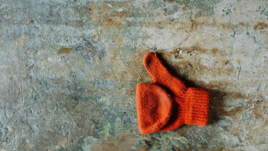 orange glove doing thumbs up sign on a brick floor