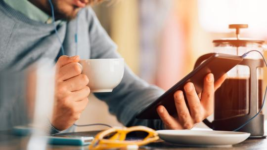 man holding coffee cup looking at tablet