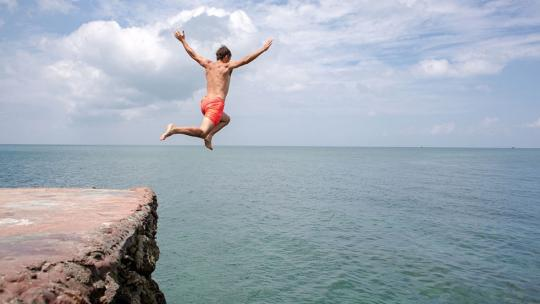 A man jumps into the ocean