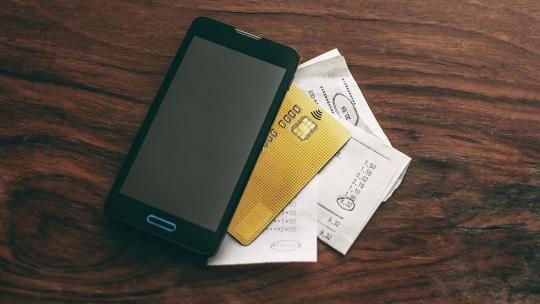 Mobile phone and credit cards on desk