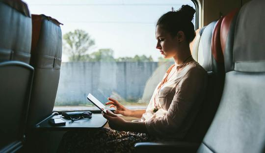 Woman sitting on train using tablet