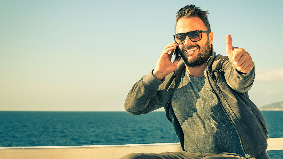 Man smiling and giving thumbs up while on the phone