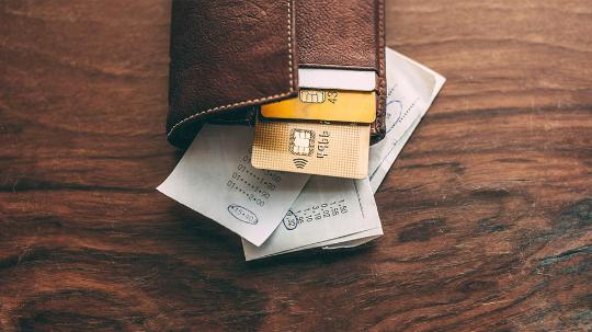 A wallet with credit cards and receipts on a table