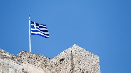 Greek flag flies on a blue sky