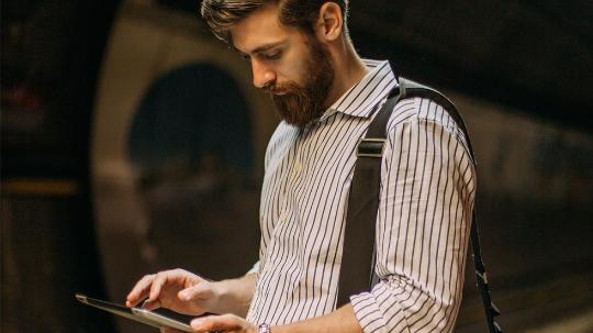 A man in shirt with shoulder bag uses a tablet for work