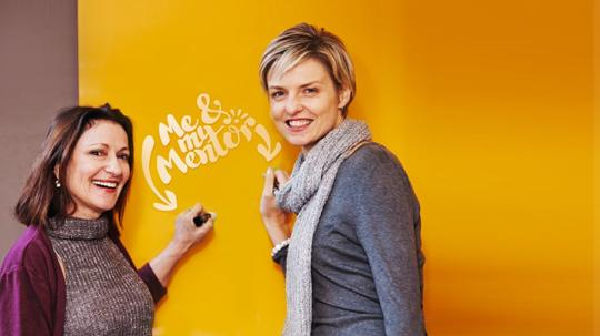 Patti Wolf and Jo-Anne Bowyer standing in front of an orange wall