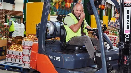 Shaun McInerney driving a forklift around the Sydney Market in work gear