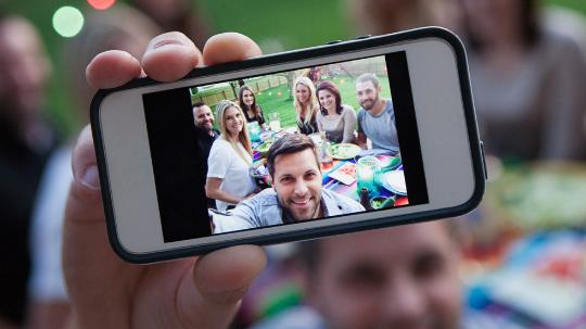 A man takes a selfie of himself and his friends