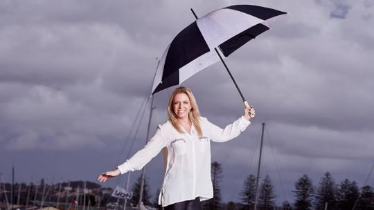 Janine Garner smiling while holding an umbrella