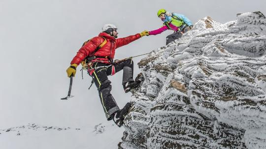 A mountain climber reaches for a woman's hand