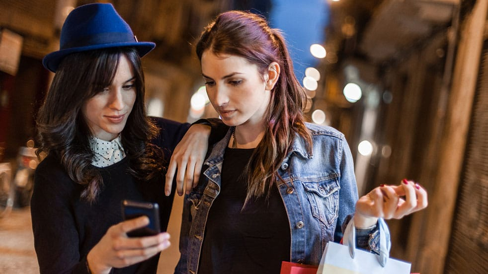 A pair of women looking at a smartphone while shopping